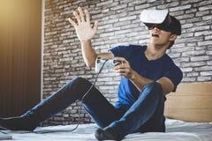 Ung man i virtuell verklighethörlurar med mikrofon eller exponeringsglas som 3d spelar videoen Royaltyfria Foton