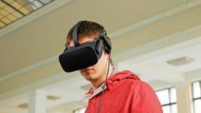 Ung man i VR-hörlurar med mikrofon som spelar den faktiska leken Arkivfoto