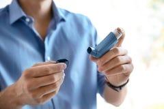 Ung man med astmainhalatorn inomhus royaltyfria bilder