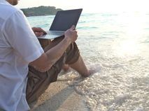 Ung man med bärbar datorsammanträde på sand av den tropiska stranden under solnedgångtid Koppla av och resa begreppet royaltyfria foton