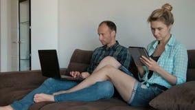 Ung man med bärbara datorn och kvinnan med minnestavlasammanträde på soffan i lägenhet arkivfilmer