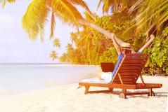 Ung man med bärbara datorn på den tropiska stranden Royaltyfria Bilder