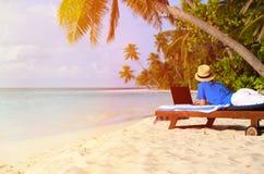 Ung man med bärbara datorn på den tropiska stranden Royaltyfri Bild