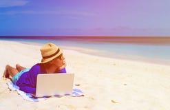 Ung man med bärbara datorn på den tropiska stranden Arkivfoton