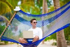 Ung man med bärbara datorn på hängmattan på tropisk semester royaltyfri fotografi