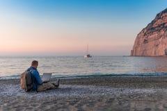 Ung man med b?rbar datorarbete p? stranden Frihet, avl?gsna arbets-, freelancer-, teknologi-, internet-, lopp- och semesterbegrep royaltyfria foton