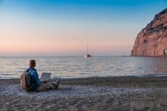 Ung man med b?rbar datorarbete p? stranden Frihet, avl?gsna arbets-, freelancer-, teknologi-, internet-, lopp- och semesterbegrep royaltyfri fotografi