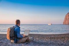 Ung man med b?rbar datorarbete p? stranden Frihet, avl?gsna arbets-, freelancer-, teknologi-, internet-, lopp- och semesterbegrep arkivbild