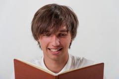 Ung man med boken Arkivfoto