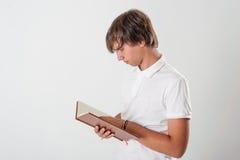 Ung man med boken Arkivbild