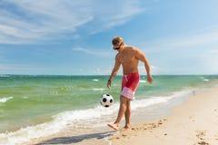 Ung man med bollen som spelar fotboll på stranden Royaltyfria Bilder