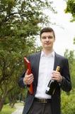 Ung man med champagne och choklader Royaltyfria Bilder