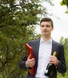 Ung man med champagne och choklader Arkivbild