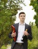 Ung man med champagne och choklader Fotografering för Bildbyråer