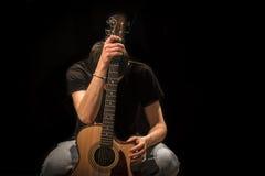 Ung man med den akustiska gitarren på svart bakgrund royaltyfri fotografi