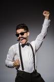 Ung man med den falska mustaschen som isoleras på grå färger Arkivbild