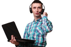 Ung man med den hållande bärbara datorn för hörlurar med mikrofon - man för appellmitt med hea Arkivfoto