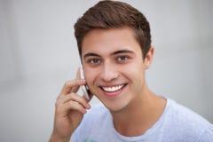 Ung man med den mobila telefonen Fotografering för Bildbyråer