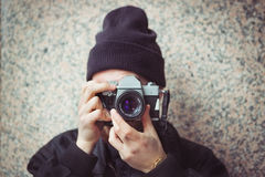 Ung man med den parallella kameran för tappning som tar en bild Fotografering för Bildbyråer