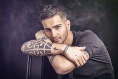 Ung man med den svarta t-skjortan och tatueringar royaltyfri fotografi