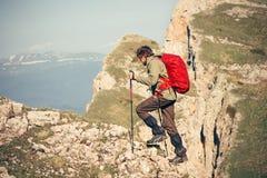 Ung man med den utomhus- ryggsäcken och trekking köra för poler Arkivfoton