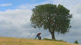 Ung man med det avslappnande near trädet för ryggsäck, fotvandrare som tycker om naturen, grön turism stock video
