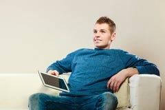 Ung man med digitalt minnestavlasammanträde på soffan Fotografering för Bildbyråer