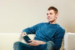 Ung man med digitalt minnestavlasammanträde på soffan Royaltyfri Bild