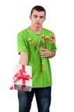 Ung man med en bukett av röda tulpan och gåvaasken Royaltyfria Bilder