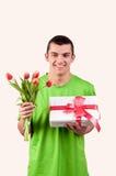 Ung man med en bukett av röda tulpan och gåvaasken Royaltyfri Bild