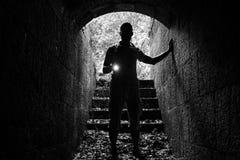 Ung man med en ficklampa i stentunnel Royaltyfria Foton