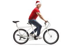 Ung man med en julhatt som rider en tandem cykel och ser kameran arkivfoton
