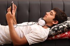 Ung man med en minnestavlaPC och hörlurar på soffan Fotografering för Bildbyråer