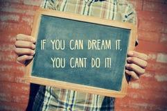 Ung man med en svart tavla med texten, om du kan drömma den, y Fotografering för Bildbyråer