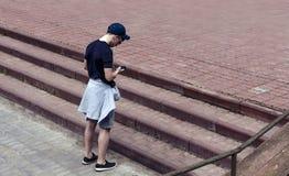 Ung man med en telefon i stadsgatan Arkivbild
