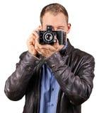 Ung man med ett läderomslag som rymmer en gammal tappningkamera och pekar på den isolerade kameran - Royaltyfri Fotografi