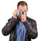 Ung man med ett läderomslag som rymmer en tappningkamera och pekar på den isolerade kameran - Royaltyfri Fotografi