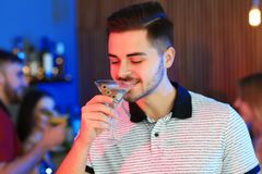 Ung man med exponeringsglas av den martini coctailen på partiet royaltyfri foto