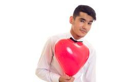 Ung man med flugainnehavballongen Royaltyfria Bilder