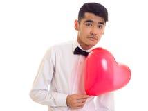 Ung man med flugainnehavballongen Royaltyfri Bild