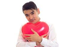 Ung man med flugainnehavballongen Royaltyfri Foto