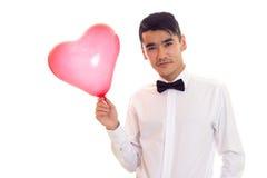Ung man med flugainnehavballongen Royaltyfri Fotografi