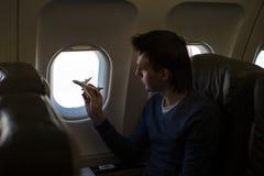 Ung man med flygplanet för liten modell inom ett stort flygplan Arkivbild