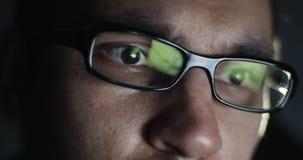 Ung man med glass arbete på bärbara datorn i mörkret lager videofilmer