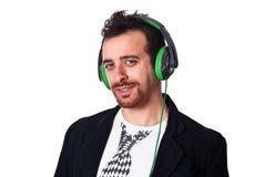 Ung man med grön hörlurar som lyssnar till musik Fotografering för Bildbyråer