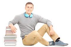 Ung man med hörlurar som lutar på bunt av böcker royaltyfri fotografi