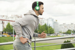 Ung man med hörlurar som utomhus joggar Royaltyfri Foto