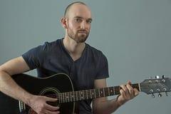 Ung man med hans akustiska gitarr Royaltyfri Fotografi