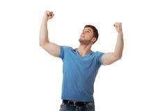 Ung man med hans armar upp i segergest Fotografering för Bildbyråer