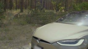 Ung man med hans flickaridning i lyxig bil nära skogen arkivfilmer